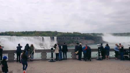 mais : Niagara Falls, Ontario, Canada. May, 2017. Groups of tourists in Niagara Falls. The waterfalls were formed during the last ice age. Stock Footage