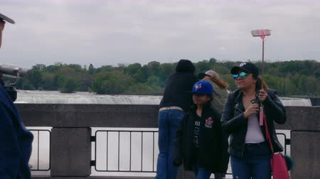 mais : Niagara Falls, Ontario, Canada. May, 2017. Groups of tourists in Niagara Falls. The American Falls is located entirely on the United States side and is the second largest of the three falls. Stock Footage