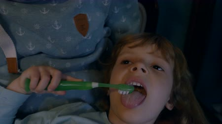 brushing : A little girl plays with a toothbrush while lying in her mothers lap. Close up.