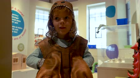 solo : A cute little girl smiles wearing an alligator suit. Medium shot.