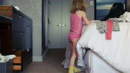 ona : A little girl gets dressed. She tries to put on a yellow sock and walks away. Long shot.