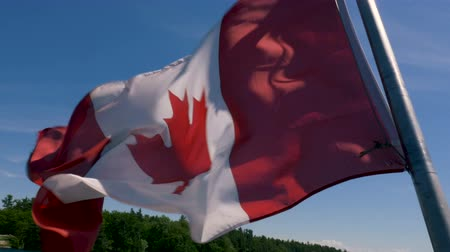gün : The Canadian flag on a boat flaps in the wind as it sails across Lake Huron.
