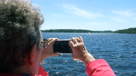 napfény : Ontario, Canada. May 2017. A woman filming the waters of Georgian Bay with her smartphone as her boat sails. By 2012 over a billion smartphones were in use worldwide.