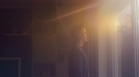ninhada : A man looks out the window as fading sunlight shines warm tawny colors onto him. Filmed from profile medium shot.