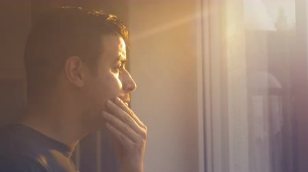 ninhada : A man looks out the window as fading sunlight shines warm tawny colors onto him. Filmed in profile and closeup. Stock Footage