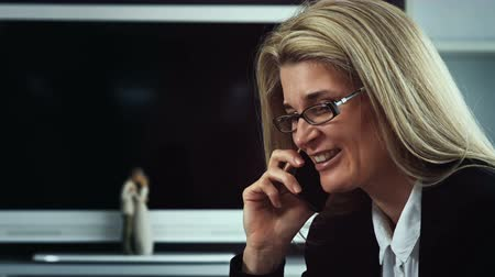 ıvır zıvır : A business woman talking on the phone filmed from close up. She smiles and looks directly into the camera Stok Video