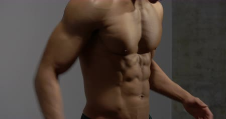 abs : The muscular torso of a fitness model is filmed from profile with a slight angle. He prepares for a work out and crosses his arms. Stock Footage