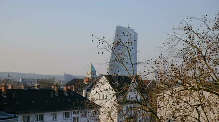 mozog e fel : Rooftops, skyscraper, and trees make up this panorama shot of Frankfurt, Germany. The camera moves to the right.