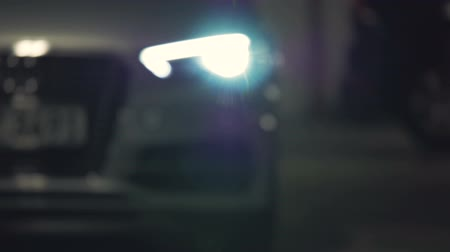 worms eye view : A car pulls up and backs out away from the camera flashing its headlights brightly. Extreme close up. Rack focus. Stock Footage
