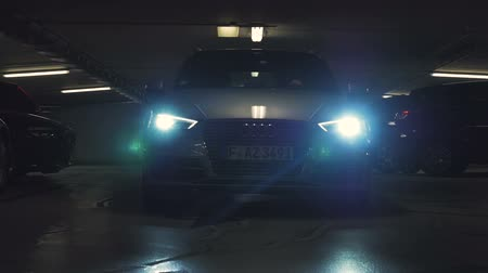 worms eye view : Frankfurt, Germany, circa 2017. The headlights of a car flashing brightly as it heads towards the camera. Close to six million cars are produced in Germany annually.