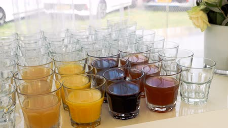 núpcias : Glasses lined up on top of a restaurant table with a few of them full of various kinds of juice and the rest empty.