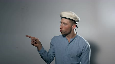 gesticulando : A young man behind a white wall wearing a beret kisses his index finer and points. Medium close up. Profile.
