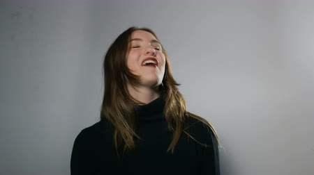 gesticulando : A young woman sitting behind a white wall makes playful facial expressions and hand signs while smiling. Medium close up. Vídeos