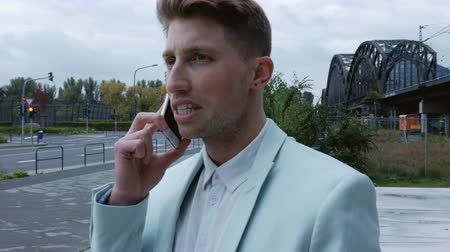 smokin : A young man wearing a turquoise tuxedo talking on a mobile phone. A cloudy street scene in the background. Medium close up. Profile.