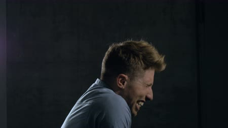 rústico : A young man screaming in pain filmed from profile. The young man is wearing a casual dress shirt and standing behind a dark grey wall. Medium close up. Profile.