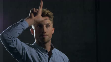 perdedor : A young man gestures towards the camera making the loser hand gesture on his forehead. The young man is wearing a casual dress shirt and standing behind a dark grey wall. Medium close up. Stock Footage