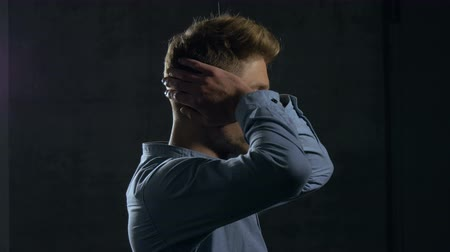 rústico : Profile of a young man covering his ears with his hands. The young man is wearing a casual dress shirt and standing behind a dark grey wall. Medium close up. Profile. Stock Footage