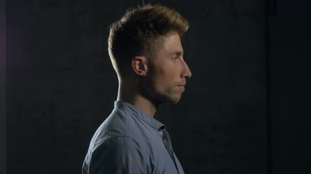 rústico : Profile of a young man covering his eyes with his hands. The young man is wearing a casual dress shirt and standing behind a dark grey wall. Medium close up. Profile.