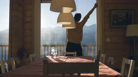faház : A man stretches out his arms on a Swiss chalet balcony in the Alps. Rear view. Stock mozgókép