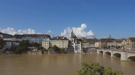 manmade : The Rhine flows gently underneath a Basel bridge. Architecture spans across the river. An bright blue sky with fluffy white clouds above. Time lapse. Stock Footage