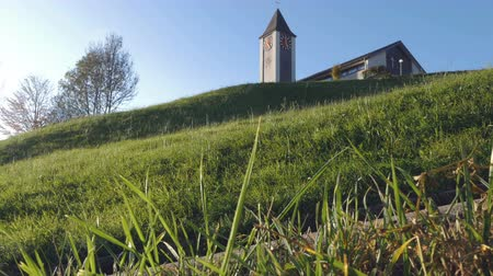 worms eye view : A small church building with a clock tower atop a grassy hill in Switzerland. A fresh sunny bright and cloudless morning. Low angle shot. Worms eye view.