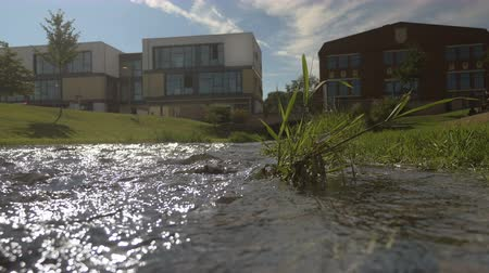 worms eye view : The waters of a small city stream. Low rise buildings and the sky in the background. Worms eye view.