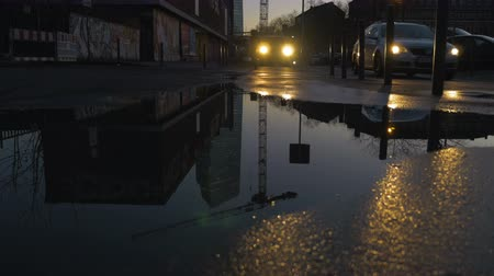 worms eye view : A cars headlight shine a golden color as they head towards the camera. A crane and a skyscraper reflect of a puddle in the early evening hours. Worms eye view. Stock Footage