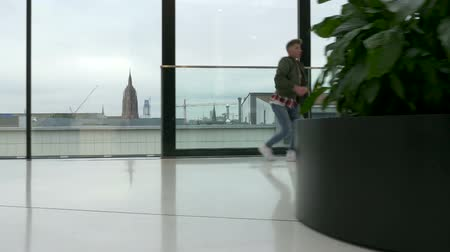 worms eye view : A dancer performs on a shiny marble floor. City architecture visible in the background through large windows. Overcast sky. Long shot.