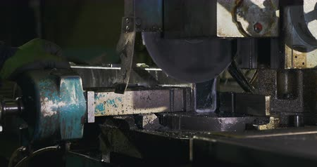 tření : A metal cutting saw at an automotive shop slowly drops down as it begins to cut a piece of metal. The camera moves to the right.