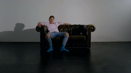 разорвал : A young male actor showing a pose of ease and relaxation sitting on a leather couch inside an empty studio. Full body shot.