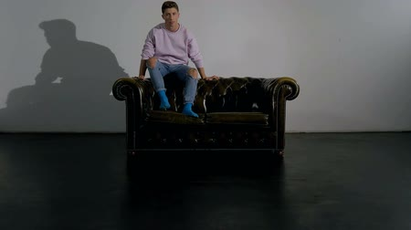 разорвал : A young man on a leather sofa inside an empty studio demonstrates various sitting positions. Long shot.