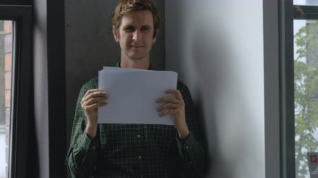 exibindo : Man Holding Up Blank Sheets of Paper and Smiling