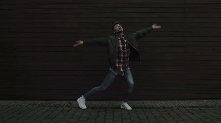 dancing people : A street dancer performing his art in front of a wooden wall and on a paved road. Full body shot. Stock Footage