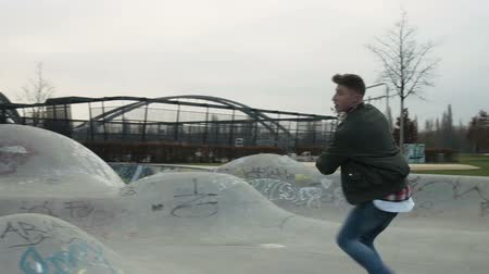 dancing people : A street dancer dancing in a skatepark. The camera a pans revealing a recreational sports arena and a city park in the background. Full body shot.
