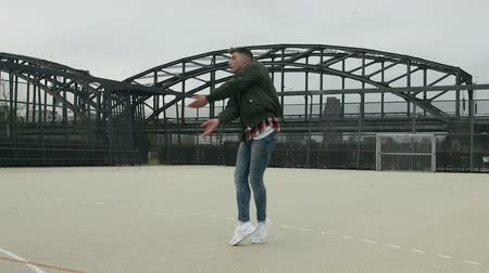 teljes test : A street dancer dancing on a hard surface outdoor soccer field. City structures in the background and overcast sky above. Full body shot. Stock mozgókép