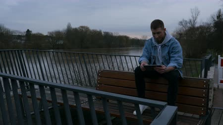 ebook : Browsing the internet using a tablet on a river pier bench. A young man reading a book on a digital tablet sitting on a pier bench. Full body shot. Angle. Front facing.