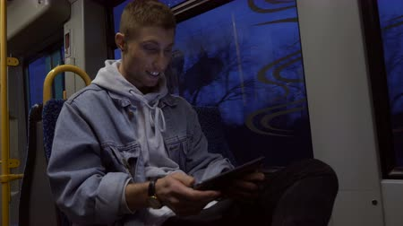 tramwaj : A happy young man using a digital tablet while commuting in a tram. Three quarter length. Low angle.