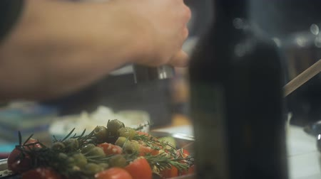 shaker : A cooks hands add black pepper to vegetables in a casserole. Tomatoes, rosemary, and olives receiving black pepper. Slow motion. Close up. Selective focus. Stock Footage