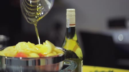 olive oil pour : Pouring oil into a metal bowl filled with raw potato slices. Close up. Slow motion. Rack focus.