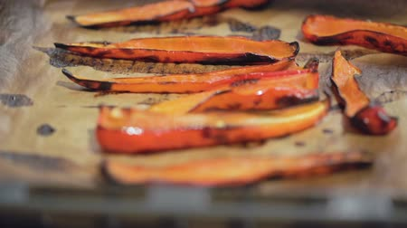 hot peppers : Slices of baked red peppers on a steaming on a baking sheet. Close up. Slow motion.