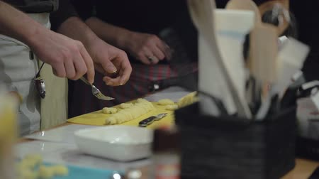 çatallar : Slow motion cooking: gnocchi pieces on a cutting board and hands of cooks. Slow motion. Close up. Hands only.