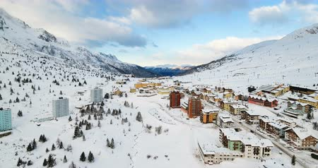 vanishing point : Flight over hotels at Passo de Tonale, Italy. Majestic snow covered mountains spread out in the horizon and all around. Drone shot. Stock Footage