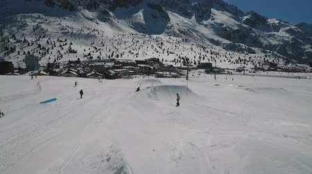 домик : A snowboarder filmed from the rear descends a slope and performs a jump off a mound. Mountain peaks stand out in the forefront. Resort lodges at the foot of the mountains.