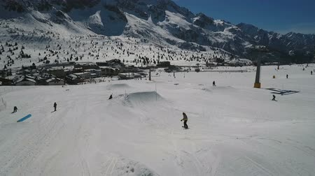 lodge : A snowboarder filmed from the rear descends a slope and performs a jump off a mound. Mountain peaks stand out in the forefront. Resort lodges at the foot of the mountains.