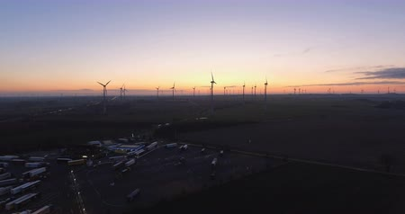 sustainable resources : Wind turbines and truck depot in colorful morning horizon. Aerial shot. Panorama.