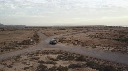 Car driving into the distance on desert road in Fuerteventura, Canary Islands. Drone shot. Stok Video