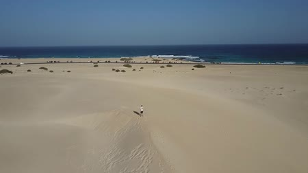 Man standing on beach sands drone shot. Camera rotating around a man standing on a Atlantic Ocean beach in Fuerteventura, Canary Islands.
