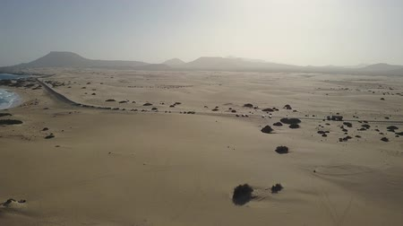 Flight over beach sands. Mountain silhouettes in the distance. Drone shot.