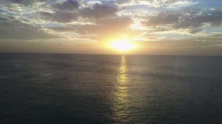 Sunset between clouds and sea. Drone shot.