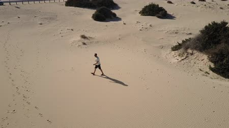Man walking and running on scorching beach sands in Fuerteventra, Canary Islands. High angle view. Aerial shot.